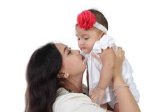 Motherly love. Young Asian mother lift and kiss her baby daughter, isolated on white background Royalty Free Stock Images