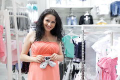 Motherly but sexy. Lovely young pregnant woman looking for some baby clothes in a store for her new baby Royalty Free Stock Photo