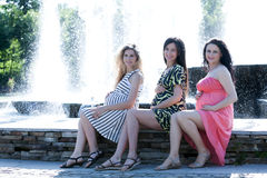 Motherly but sexy. Three young pregnant women having fun against a fountain in the park Royalty Free Stock Image