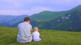 Motherm och den lilla sonen sitter och ser berg lager videofilmer