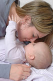 A Mothers Affection. A mom nuzzles with her baby. A mother showing affection to her baby child. Interaction between a child and parent Stock Photos