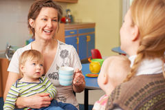 Mothers With Babies Chatting And Drinking Coffee At Playgroup Stock Photos