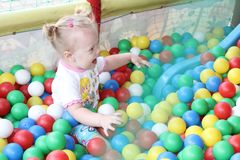 Mothers with babies plays in dry swimming pool and sits on the colored plastic balls stock photos