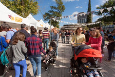 Mothers with baby carriages stroll through the bustling city street during festival Royalty Free Stock Photos