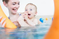 Mothers being happy about their babies playing with each other in pool royalty free stock photos
