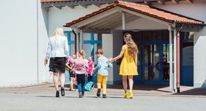 Mothers bringing the kids to school in the morning. Walking towards the entrance stock photography