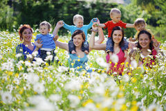 Mothers with children. In flower field Royalty Free Stock Photo