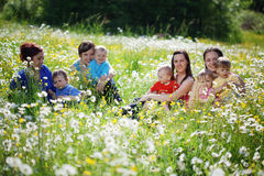 Mothers with children. In flower field Stock Images