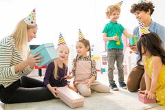 Mothers and children guessing what is inside of gift box stock photography