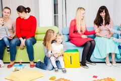 Mothers and children. Mothers with their children in the room. Women are talking and toddlers are playing Royalty Free Stock Image