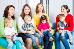 Mothers and children. Mothers with their children in the room. Women are talking and toddlers are sitting on the knees Royalty Free Stock Photography