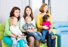 Mothers and children. Mothers with their children in the room. Women are talking and toddlers are sitting on the knees Royalty Free Stock Photos