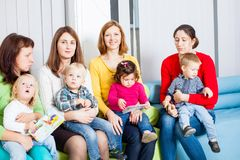 Mothers and children. Mothers with their children in the room. Women are talking and toddlers are sitting on the knees Stock Photography
