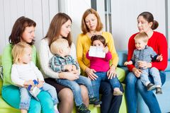 Mothers and children. Mothers with their children in the room. Women are talking and toddlers are sitting on the knees Stock Images