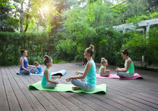 Mothers and daughters doing exercise practicing yoga outdoors Royalty Free Stock Photography