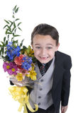 Mothers Day 01. Image of small boy dressed in suit presenting flowers as a gift Royalty Free Stock Image
