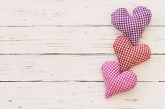 Mothers Day background with hearts border on white wood with copy space. Romantic fabric hearts border for Valentine card on white wood background royalty free stock image