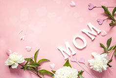 Mothers day background with white peonies and decorative hearts. On pink table. Space for text Stock Photo