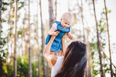 Mothers Day. A beautiful young Caucasian woman mommy holds on her hands, throws up lifts on her hands up daughter in the summer in stock photos