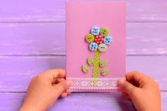 Child holds a flower card in his hands. Child made a greeting card for mom or dad. Birthday, Mothers Day, Fathers Day gift idea. Mothers day cards to make in stock images