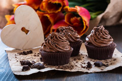 Mothers day  chocolate cupcakes  with spring tulips and wooden h Royalty Free Stock Photography