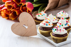 Mothers day  chocolate cupcakes  with spring tulips and wooden h Stock Photo