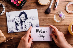 Mothers day composition. Black-and-white picture and make up pro. Black-and-white picture of mother hugging her daughters and various make up products. Hands of royalty free stock photo
