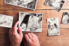 Mothers day composition. Black-and-white pictures, wooden backgr. Mothers day composition. Hands of unrecognizable men holding black-and-white photo. Studio shot royalty free stock photo