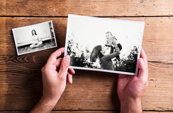 Mothers day composition. Black-and-white pictures, wooden backgr. Mothers day composition. Hands of unrecognizable men holding black-and-white photo. Studio shot royalty free stock image