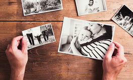 Mothers day composition. Black-and-white pictures, wooden backgr. Mothers day composition. Hands of unrecognizable men holding black-and-white photos. Studio royalty free stock photography