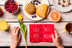 Mothers day composition. Greeting card and breakfast meal. Mothers day composition. Hands of unrecognizable woman holding greeting card with You are the best Royalty Free Stock Image