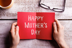 Mothers day composition. Hands of mom holding greeting card Royalty Free Stock Photos