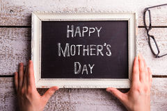 Mothers day composition. Hands of mom holding picture frame Royalty Free Stock Images
