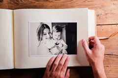 Mothers day composition. Photo album, black-and-white picture. W. Mothers day composition. Hands of unrecognizable men holding a photo album, black-and-white Royalty Free Stock Images