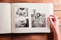 Mothers day composition. Photo album, black-and-white pictures. Mothers day composition. Hands of unrecognizable men holding a photo album, black-and-white stock photo