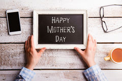 Mothers day composition. Picture frame with sign, studio shot. Hands of unrecognizable woman holding white picture frame with chalk Happy mothers day sign Stock Image