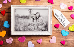 Mothers day composition, picture frame. Studio shot, wooden, bac. Mothers day composition.  Photo of mother with her daughters in picture frame. Colorful fabric Royalty Free Stock Images