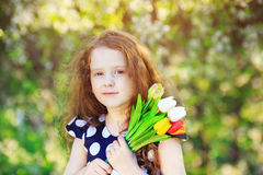 Mothers day concept, cute little girl with bouquet of tulips on Royalty Free Stock Photography