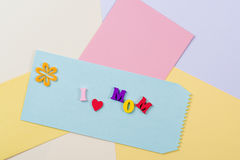 Mothers Day concept. I love mom spelled with colorful wooden letters on paper background. Stock Photography