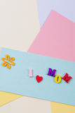 Mothers Day concept. I love mom spelled with colorful wooden letters on paper background. Royalty Free Stock Images