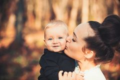 Mothers day concept. Mother kiss little son with love. Woman hug child. Mom and baby boy outdoor. Happy family enjoy