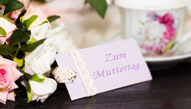 Mothers day deutch congratulation card and roses on wooden board. Mothers day card with rustic roses on wooden board Stock Images