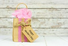Mothers Day gift bag with tag against rustic white wood Stock Photos