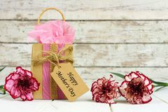 Mothers Day gift bag, tag and flowers against white wood Royalty Free Stock Image