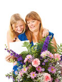 Mothers Day Gift. Mom receives flowers and a card from her daughter on Mother's Day.  Could also work as a birthday concept Stock Photo