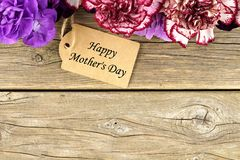 Mothers Day gift tag with flower top border on wood Royalty Free Stock Photos