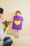 Mothers day, girl giving flowers and card to her mum Royalty Free Stock Photo