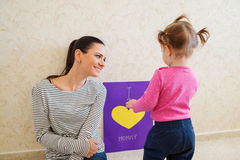 Mothers day, girl giving greetingcard to her mum. Mothers day, cute little girl giving a greeting card with I love you mommy sign to her mother Stock Image