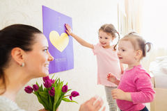 Mothers day, girls giving flowers and card to their mum Stock Photos