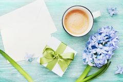 Mothers Day greeting background with holiday postcard, flowers, gift or present box and cup of coffee on table top view. Mothers Day greeting background with stock photography